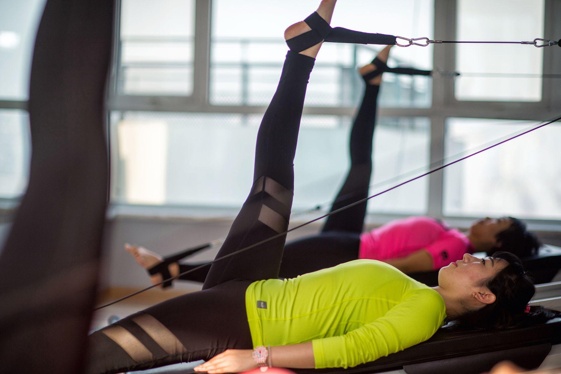 Asiatische Frau macht Pilates Übungen mit Studiogeräten